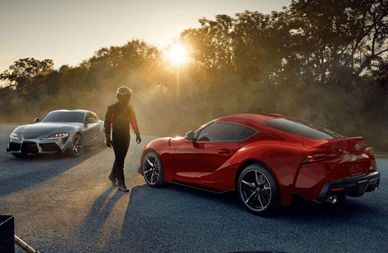 Two 2020 Toyota Supra models with a driver walking in between