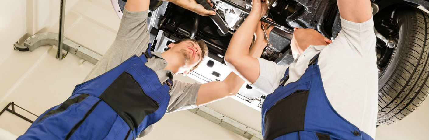 Two Service Representatives Working on Underbody of Car