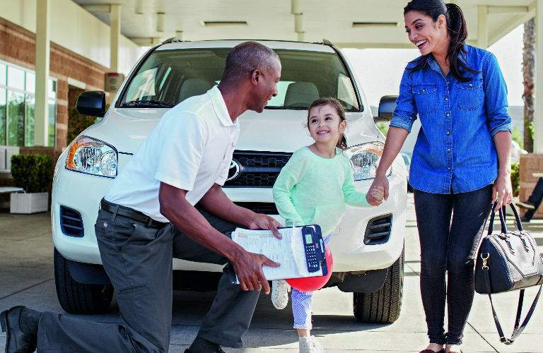 Toyota Service Tech Talking to Mom and Child by Vehicle