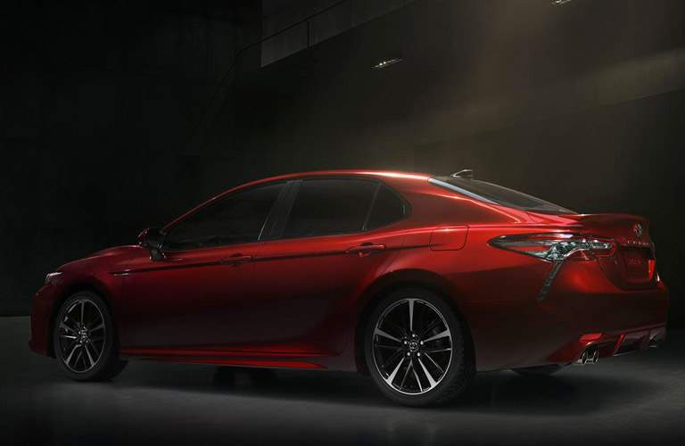 Profile shot of red 2018 Toyota Camry parked on dark street with light illuminating in rear
