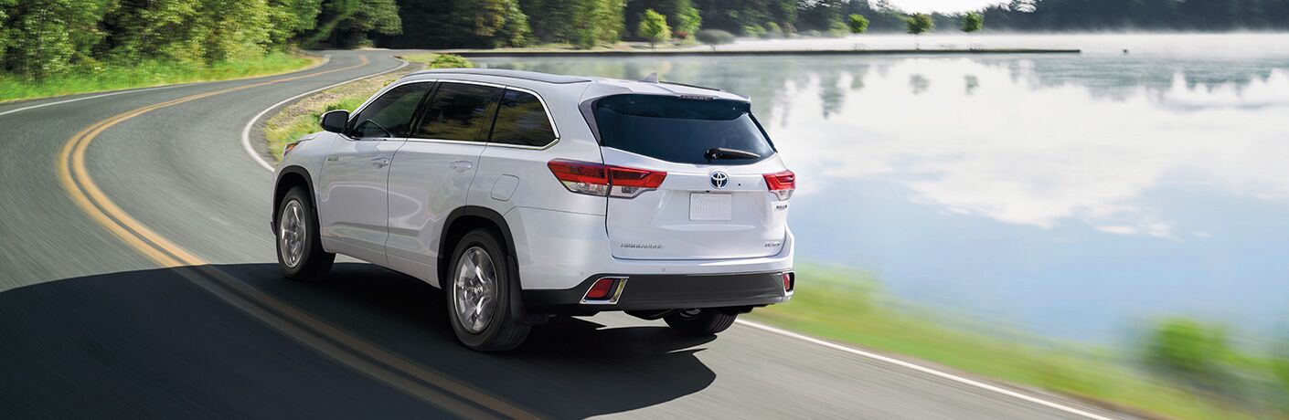 Rear driver side exterior view of a white 2019 Toyota Highlander