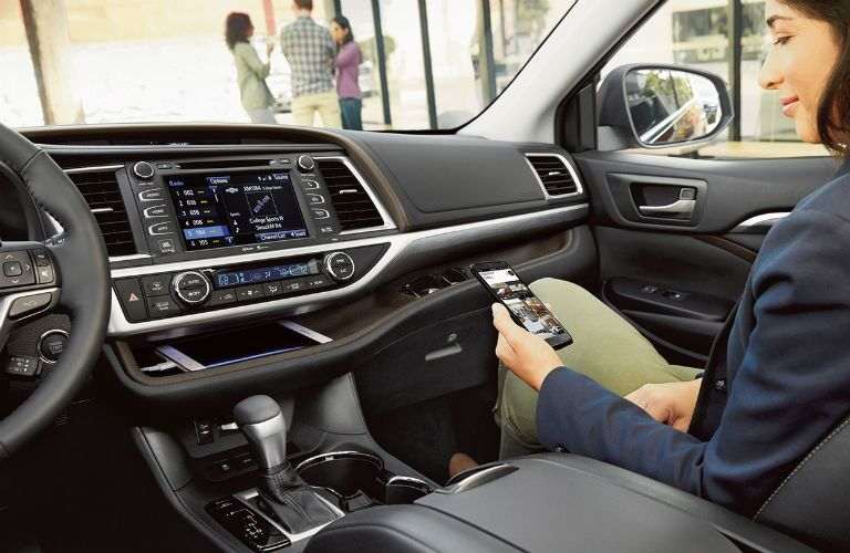 Woman connecting her smartphone to the touchscreen display of the 2019 Toyota Highlander