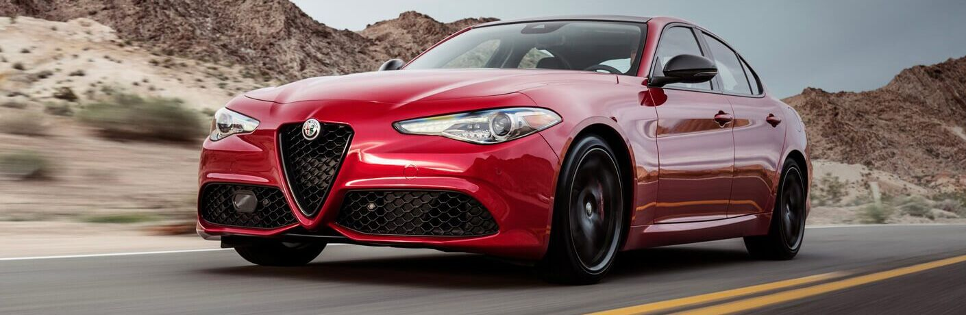 front side view of a 2018 Alfa Romeo Giulia sport sedan in red, driving on the road