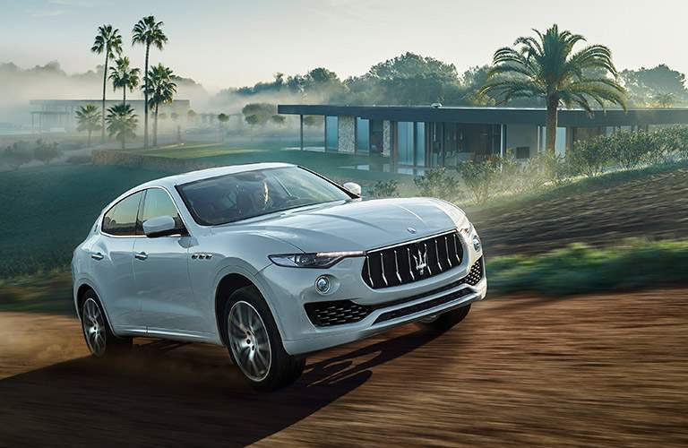 white 2017 Maserati Levante driving by a house with palm trees