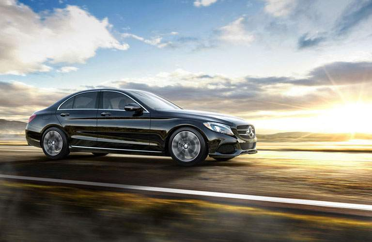 side view of a black 2017 Mercedes-Benz C-Class driving in the sunset