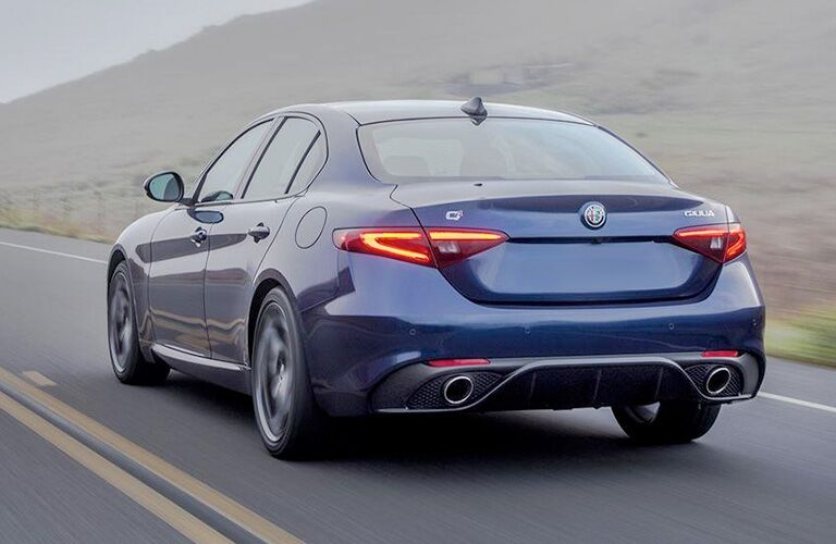rear view of a blue 2018 Alfa Romeo Giulia driving in fog