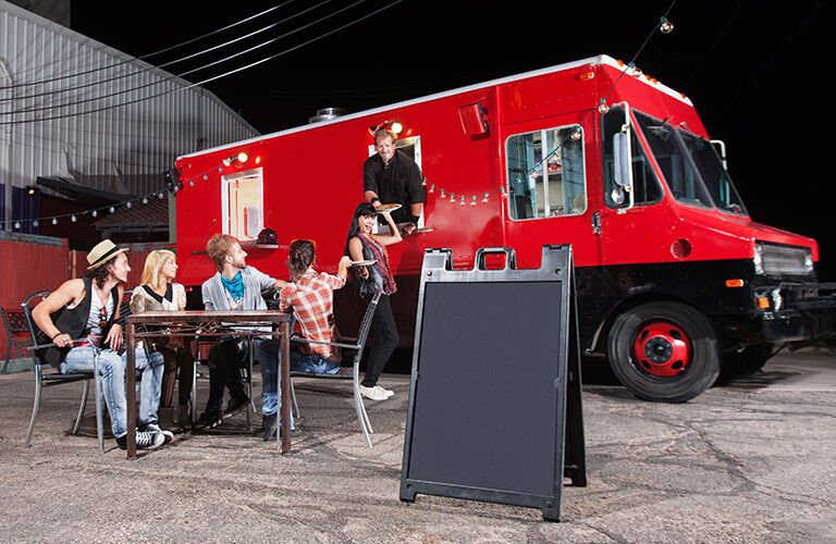 people eating from a red food truck