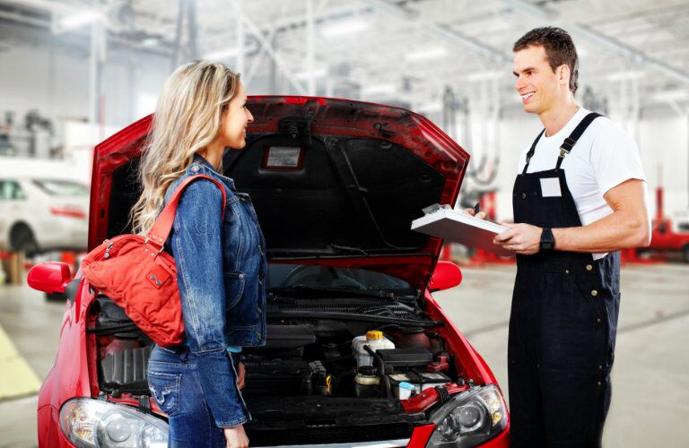 mechanic and vehicle owner smiling at each other