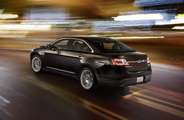 Black 2013 Ford Taurus driving