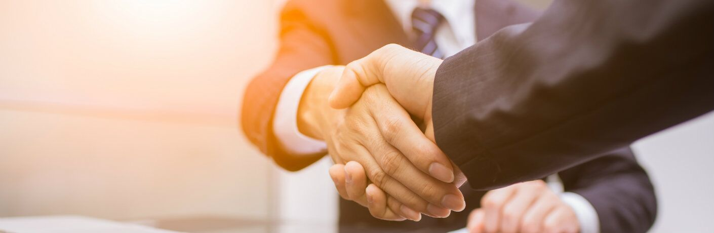 Arms of men in business suits shaking hands