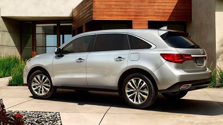 2015 Acura MDX exterior back fascia and drivers side parked next to building