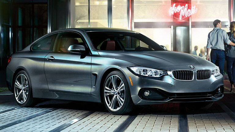 2015 BMW 4 series exterior front fascia and passenger side in front of restaurant with couple to the side