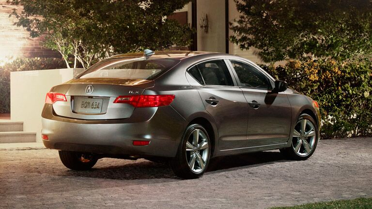 2015 Acura ILX exterior back fascia and passenger side parked on driveway with trees and sunlight