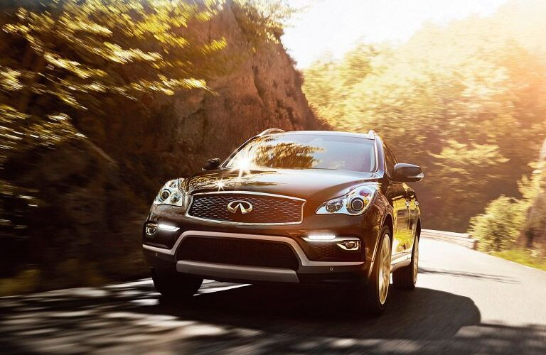 2016 Infiniti QX50 exterior front fascia and partial drivers side driving on road with trees
