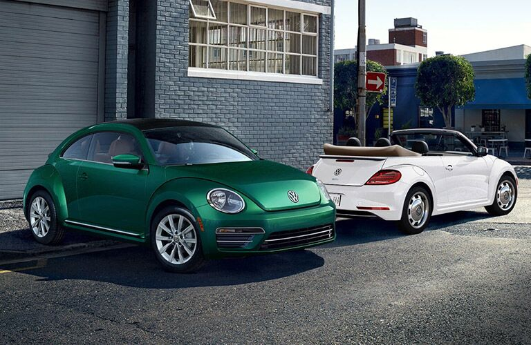 Green and white Volkswagen Beetle Models parked next to eachother
