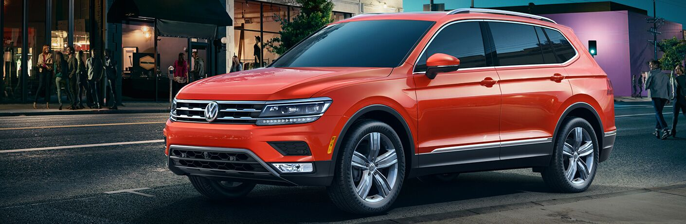 side profile of orange 2018 Volkswagen Tiguan parked outside of downtown restaurant at night