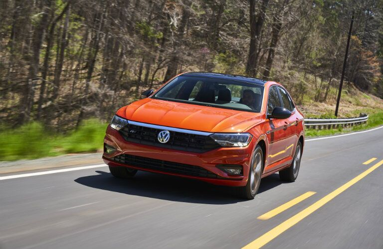 Orange 2019 VW Jetta driving on a country road