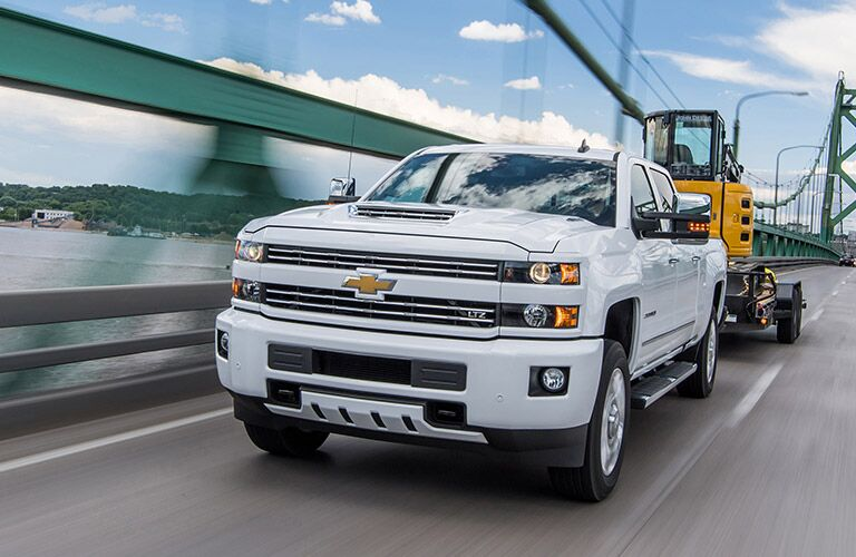 2019 Chevy Silverado 2500HD white front view towing construction equipment