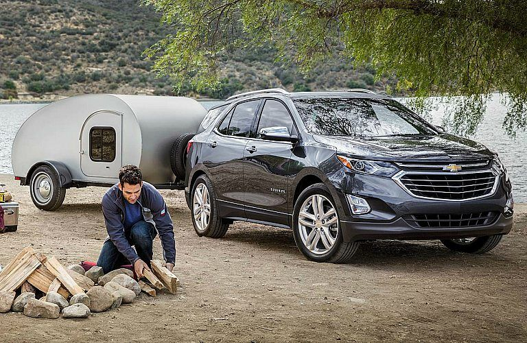 2018 Chevy Equinox black towing a small camper
