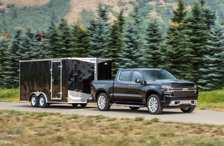 2019 Chevy Silverado 1500 black side view with a trailer