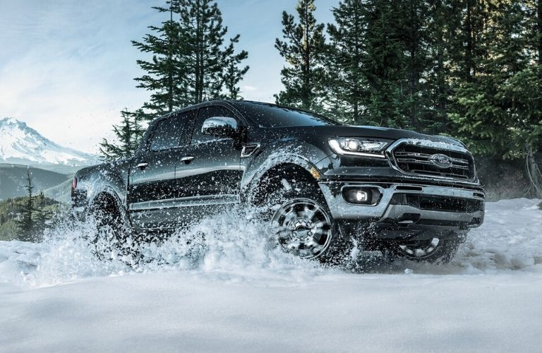 Exterior view of a black 2020 Ford Ranger driving through deep snow