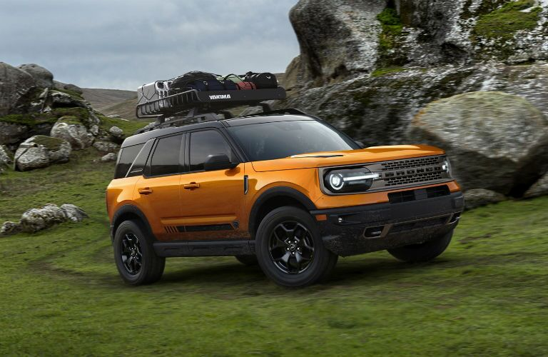The front and side view of an orange 2021 Ford Bronco Sport driving in rough terrain.