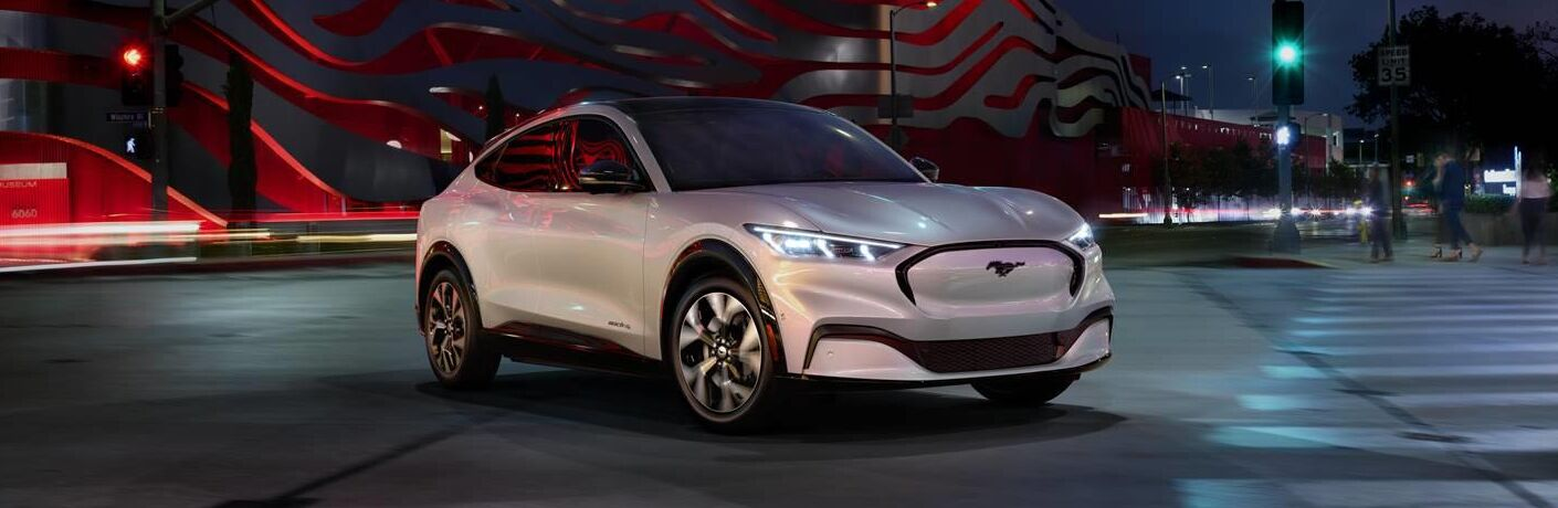 2021 Ford Mustang Mach-E all-electric SUV exterior shot with white paint color parked in front of a crosswalk at night