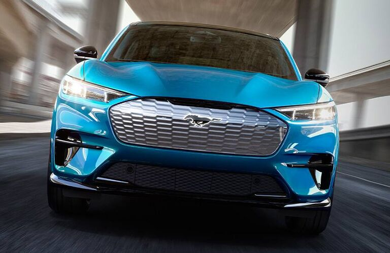 2021 Ford Mustang Mach-E all-electric SUV exterior closeup shot of headlights, grille, and front bumper with light blue paint color