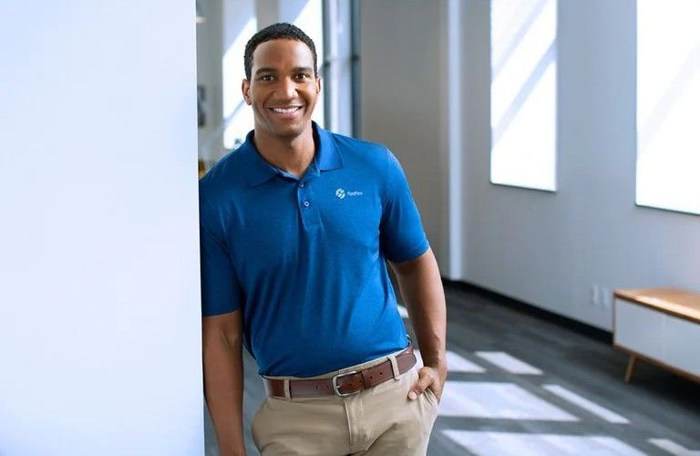 A man in a blue shirt leaning against a wall