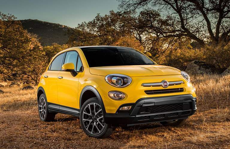 Yellow Fiat 500x parked on dirt trail with trees and mountain in background