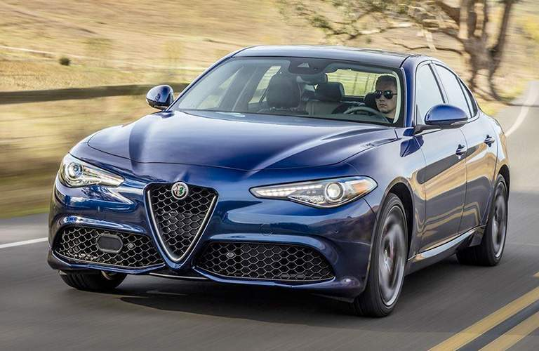 Man driving blue 2018 Alfa Romeo Giulia in fielded road