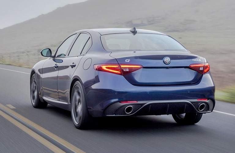 Rear view of blue 2018 Alfa Romeo Giulia driving on country road