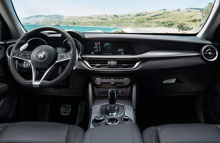 Front row of seating in 2018 Alfa Romeo Stelvio with steering wheel and center touchscreen prominently displayed