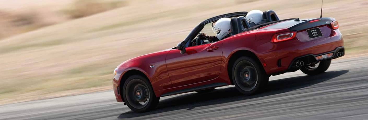Two people driving a red 2018 Fiat 124 Spider on track