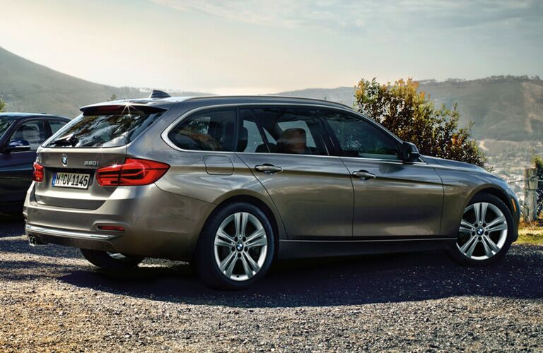 Pewter BMW 3-Series wagon parked in front of mountainous formation