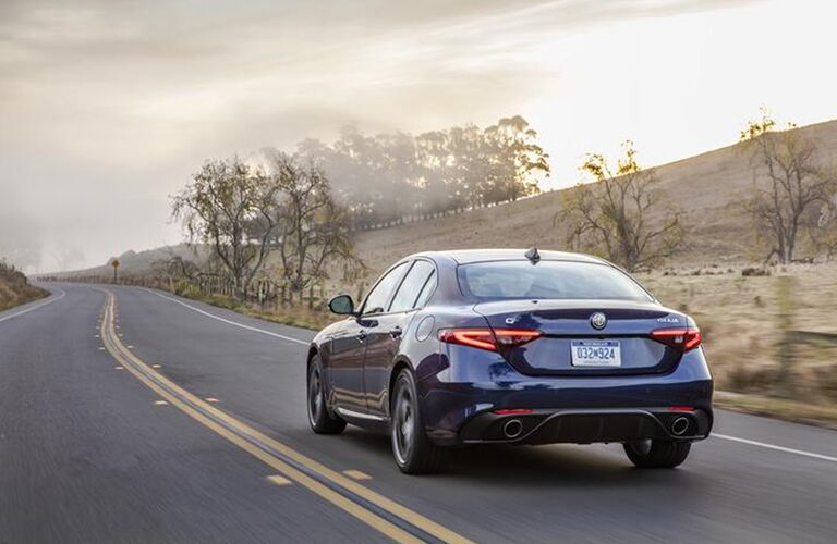 2019 Alfa Romeo Giulia exterior rear shot with dark blue paint color driving down a barren country highway near fields of winter grass and bare trees