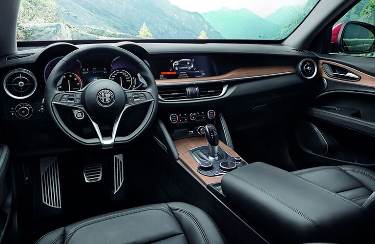 2019 Alfa Romeo Stelvio interior shot of front seating, steering wheel, transmission, and dashboard design and accent trimming
