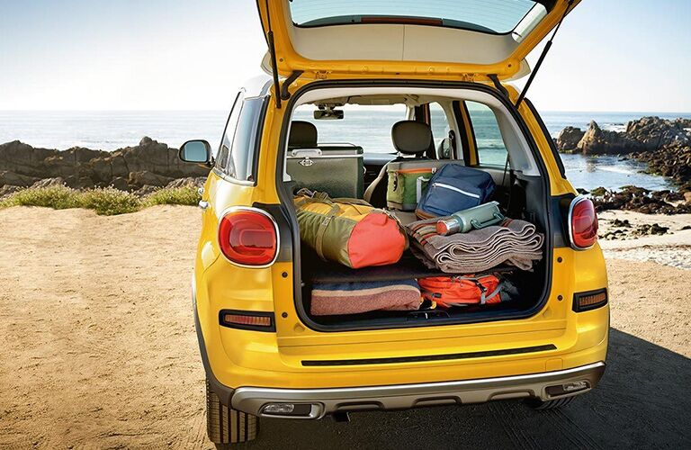 rear view of yellow 2019 fiat 500l with luggage in cargo volume