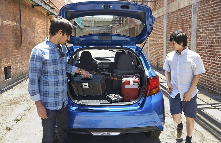 Two men unloading trunk of blue 2016 Toyota Yaris