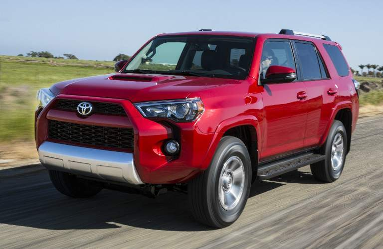 Red 2018 Toyota 4runner Driving Down Road Exterior Front Driver Side View