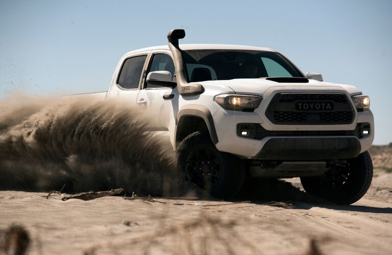 White 2019 Toyota Tacoma TRD Pro driving through dirt