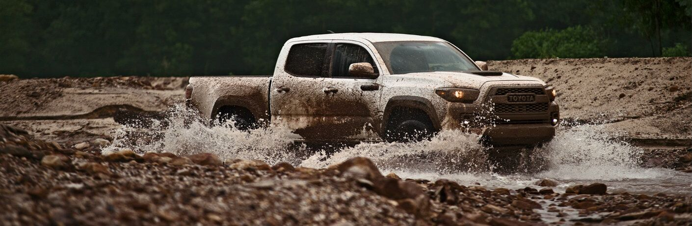 Profile view of white 2019 Toyota Tacoma TRD Pro driving through mud