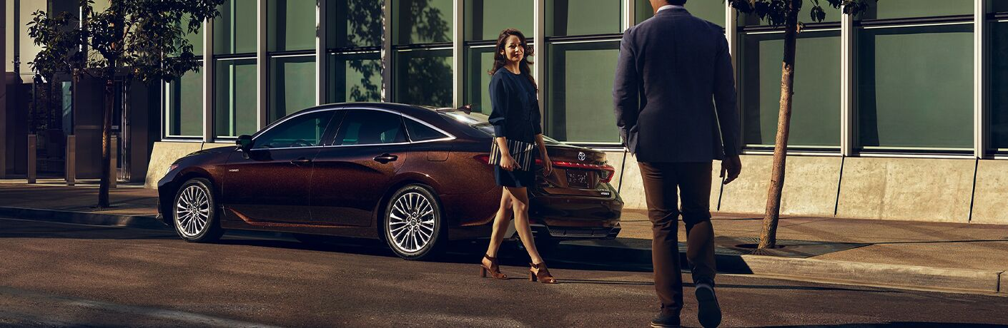 Two people walking by 2020 Toyota Avalon Hybrid