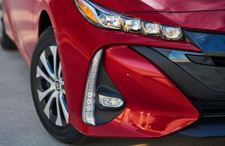 Closeup of wheel and headlight on red 2020 Toyota Prius Prime