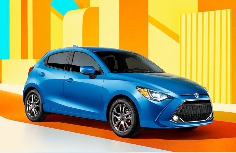 Blue 2020 Toyota Yaris Hatchback in front of orange and yellow background