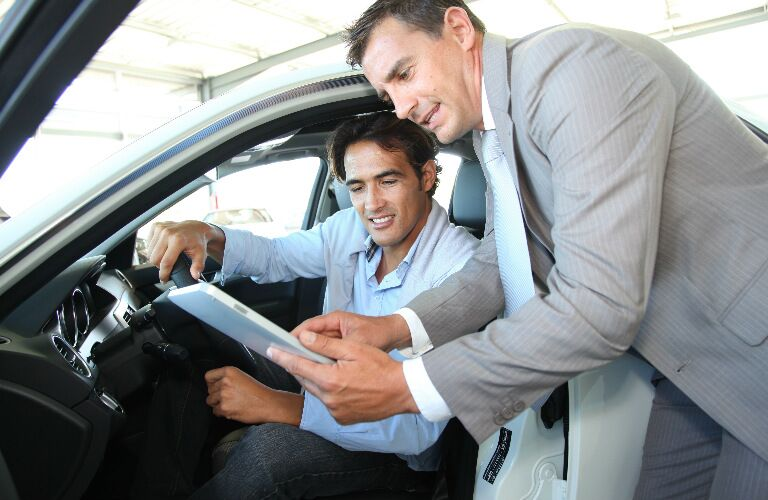 Car shopper and car dealer looking at a tablet