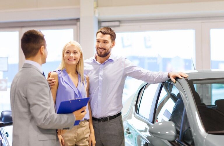 A photo of people working with a dealership's sales staff to buy a car.