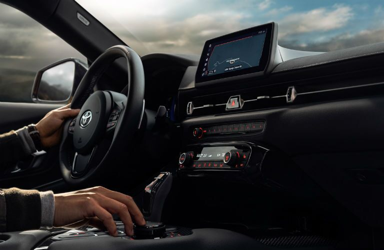 A photo of a person using the infotainment system in the 2020 Toyota Supra.