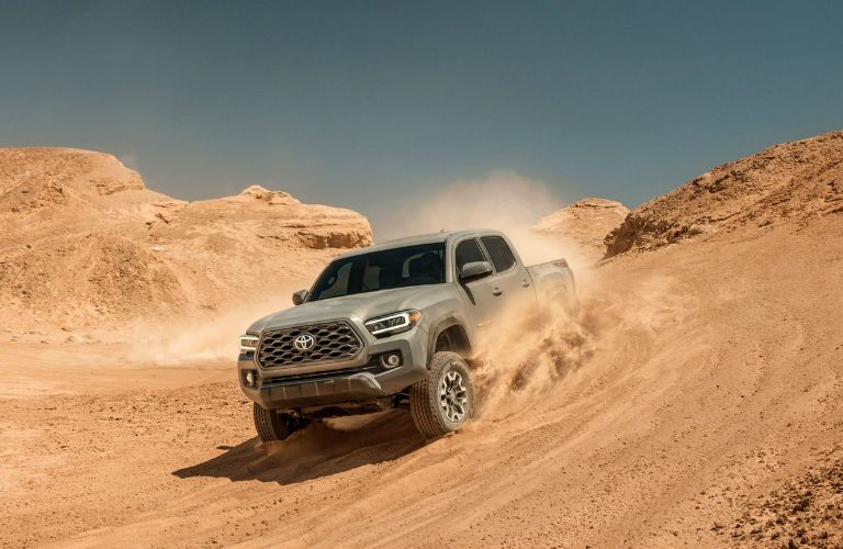 A photo of a 2020 Toyota Tacoma TRD-branded truck coming down a desert hill.