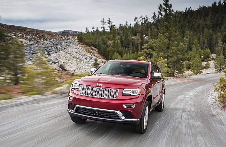 red 2015 jeep grand cherokee driving through mountain road